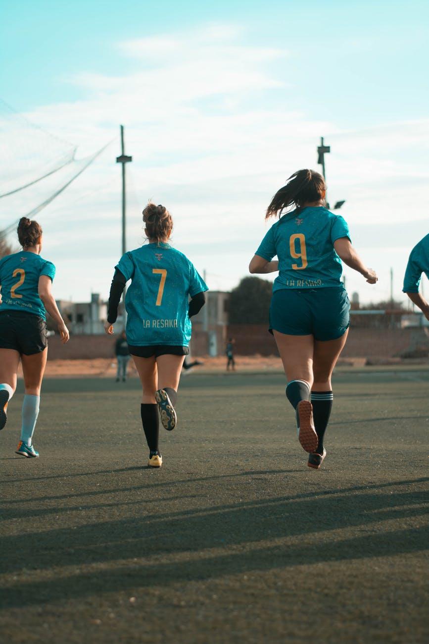 three women wearing blue jersey shirt running