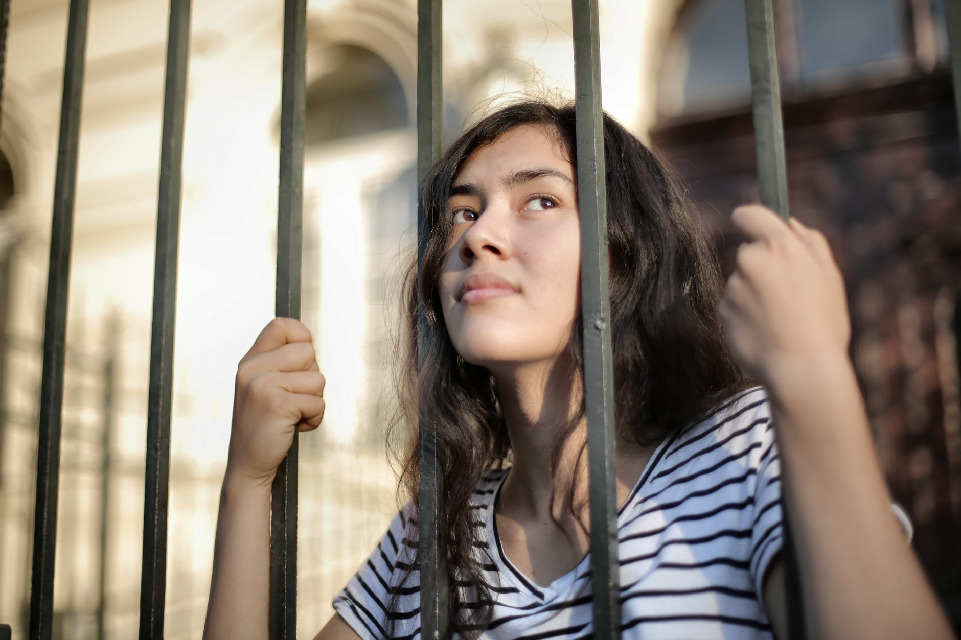 sad isolated young woman looking away through fence with hope